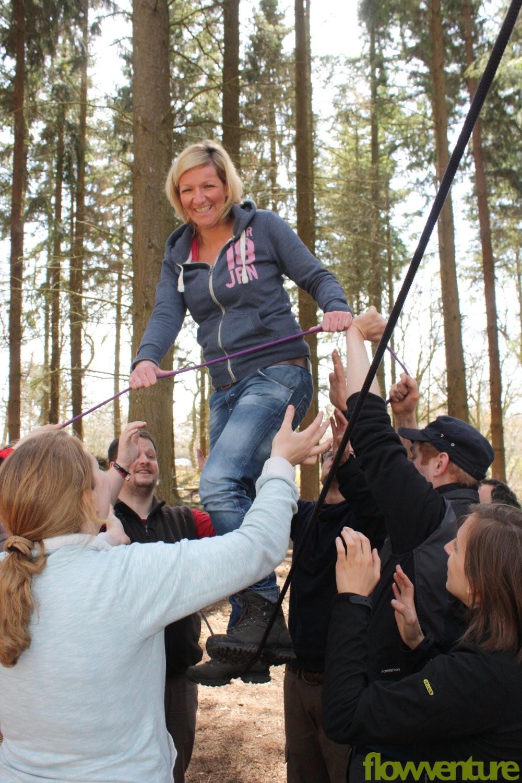Frau meistert Seilbrücke mit Teamunterstützung